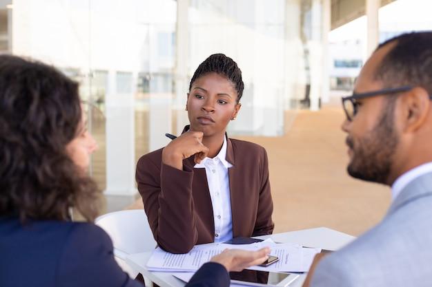 Multi-etnische zakelijke partners die contractvoorwaarden bespreken Gratis Foto