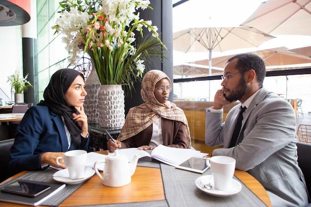 Multi-etnische zakelijke partners werken aan een overeenkomst Gratis Foto