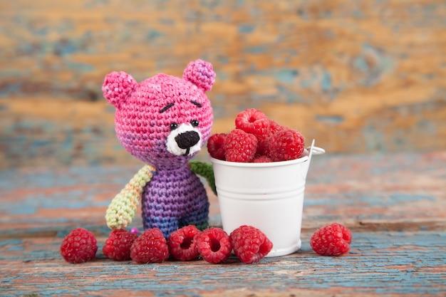 Multicolored gebreide kleine beer met bes op een oude houten achtergrond. handgemaakt, gebreid speeltje. amigurumi Premium Foto