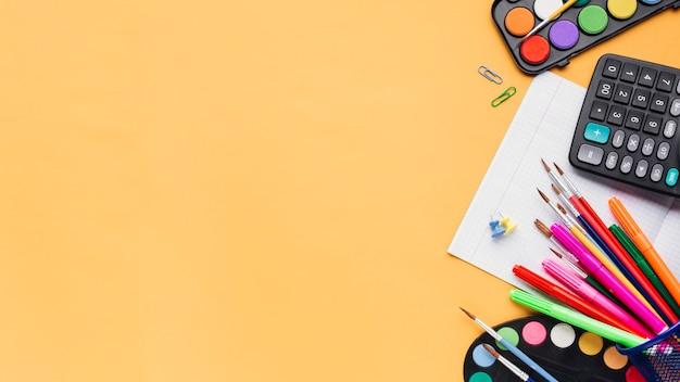 Multicolored kantoorbehoeften en calculator op beige achtergrond Gratis Foto