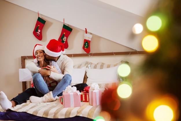 Multicultureel paar in slaapkamer knuffelen en zoenen zittend op bed Premium Foto