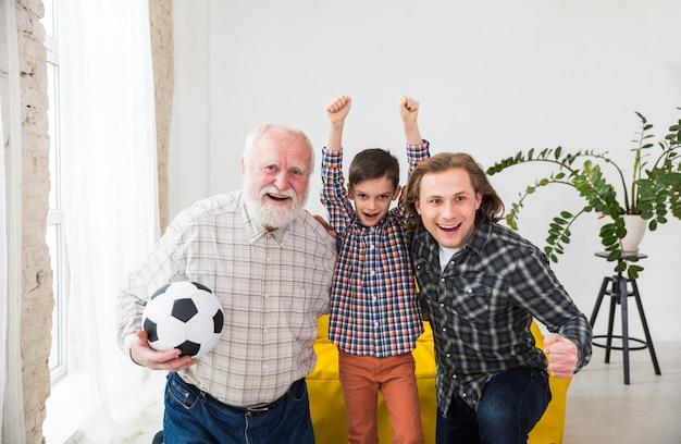 Multigeneratie-mannen die televisie kijken ondersteunen voetbalteam Gratis Foto