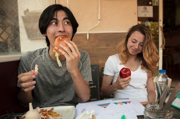 Multiraciaal jong paar die snel voedsel eten dichtbij lijst met diagrammen Gratis Foto