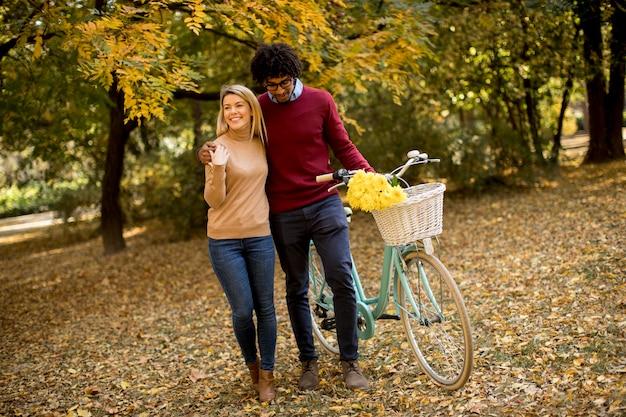 Multiraciaal paar met fiets die in het de herfstpark loopt Premium Foto