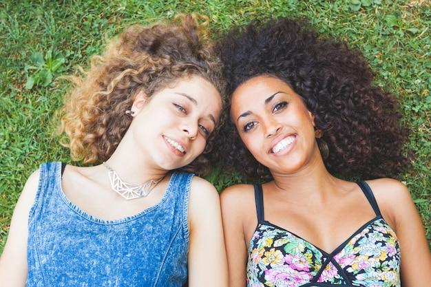 Multiraciaal vrouwelijk paar vrienden die op het gras liggen Premium Foto