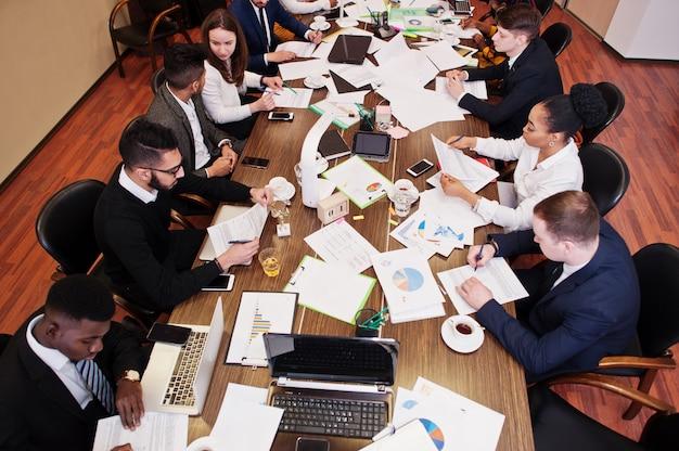 Multiraciaal zakelijk team dat vergadering rond directiekamertafel behandelt, samenwerkt en iets op papier schrijft. Premium Foto