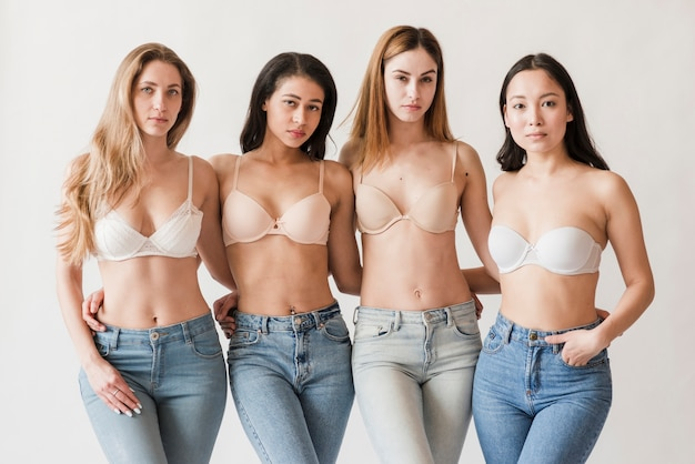 Multiraciale groep jonge vrouwen die bustehouders dragen die camera bekijken Gratis Foto
