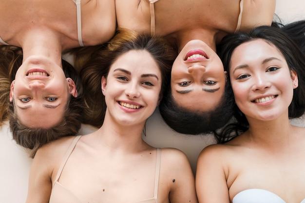 Multiraciale groep van vrolijke jonge vrouwen liggend op de rug Gratis Foto