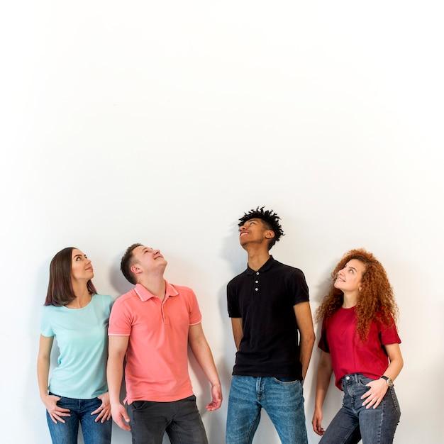 Multiraciale mensen die zich op een rij tegen het witte oppervlak opstaan Gratis Foto