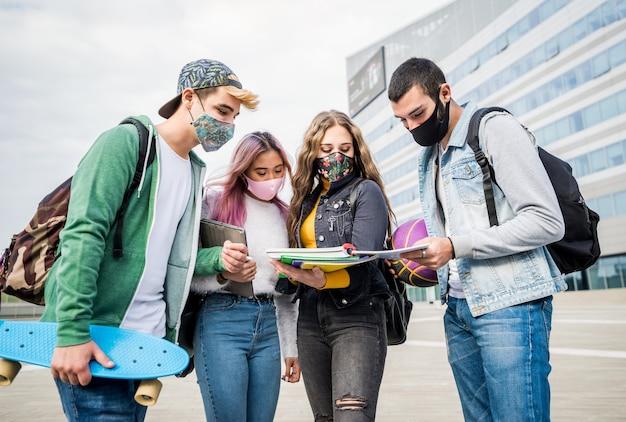 Multiraciale studenten met gezichtsmasker studeren aan de universiteitscampus Premium Foto