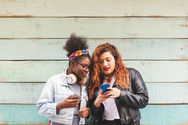 Multiraciale tiener meisjes met mobiele telefoon buitenshuis. Premium Foto
