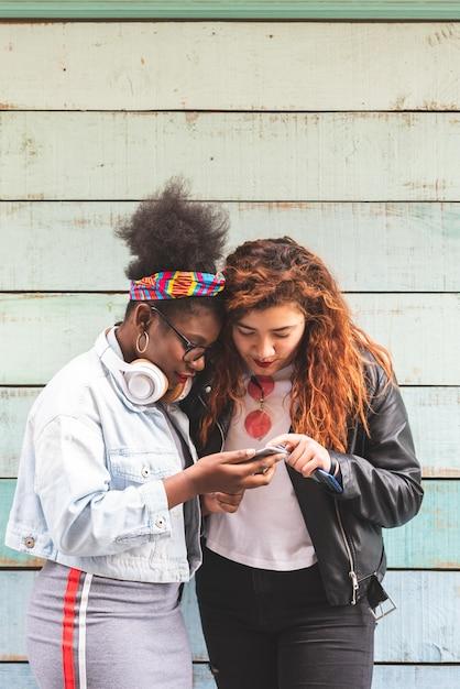 Multiraciale tiener meisjes met mobiele telefoon buitenshuis Premium Foto