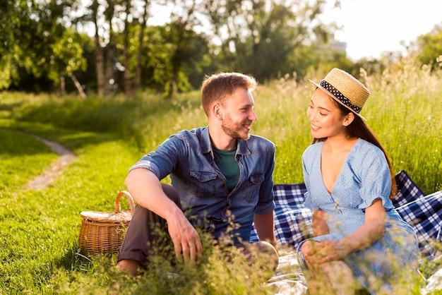 Multiraciale verliefd paar zittend op geruite plaid op met gras begroeide weide Gratis Foto