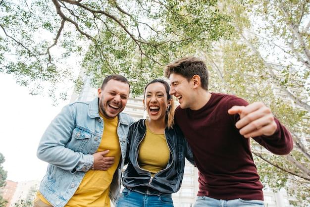 Multiraciale vrienden in vrijetijdskleding lachen Gratis Foto