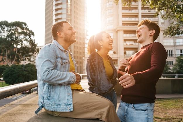 Multiraciale vrienden lachen bij zonsondergang Gratis Foto