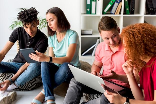 Multiraciale vrienden met behulp van elektronische gadgets zittend op de vloer met discussie Gratis Foto