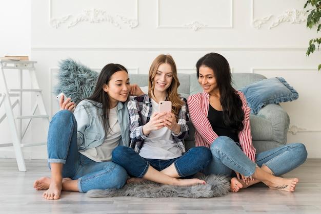 Multiraciale vriendinnen gefotografeerd op telefoon Gratis Foto