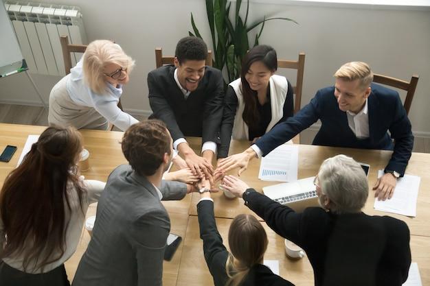 Multiraciale zakenmensen zetten handen samen op groepsteam vergadering Gratis Foto