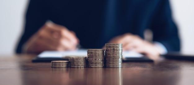 Munt om geld te stapelen, financiële bedrijfsgroei. mannen ondertekent documenten. Premium Foto