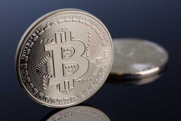 Munt van cryptomunt bitcoin op een grijs-blauwe achtergrond met reflectie onderworpen goud uitwisseling piramide op geld in verband met de groei of val wisselkoers close-up. Premium Foto