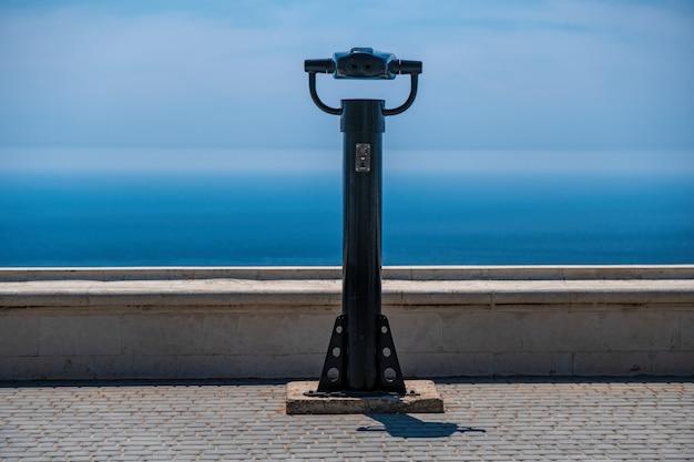 Muntautomaat verrekijker en blauwe zee achtergrond. openbare panoramische verrekijker om het uitzicht op zee te observeren. Premium Foto