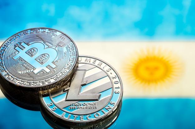 Munten bitcoin en litecoin, tegen de achtergrond van de vlag van argentinië, concept van virtueel geld, close-up. conceptueel beeld. Gratis Foto
