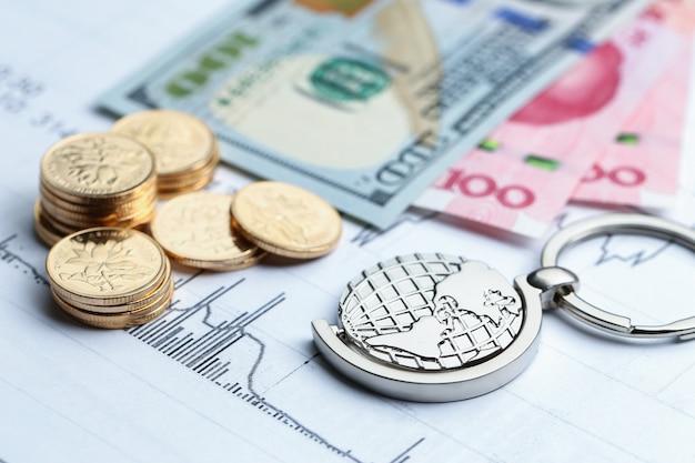 Munten, papiergeld en wereldbol op wit statistische vorm achtergrond Gratis Foto
