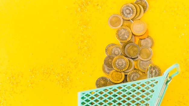 Munten verspreid uit boodschappenkar Gratis Foto