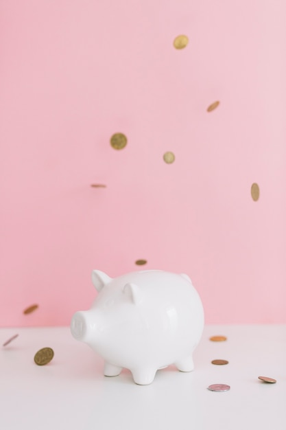 Muntstukken die over witte piggybank tegen roze achtergrond vallen Gratis Foto