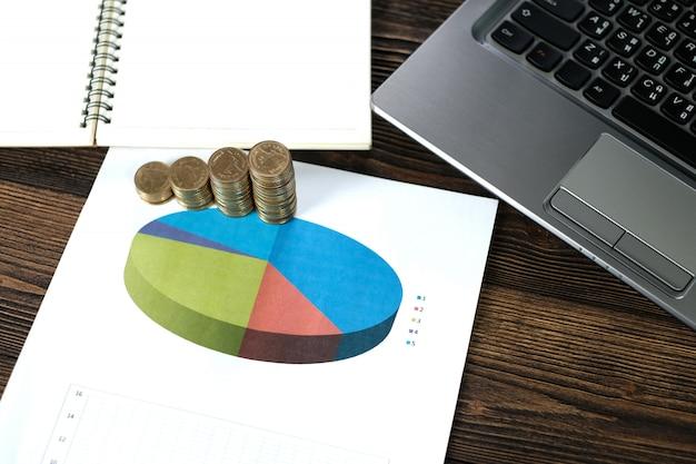 Muntstukkenstapels met notitieboekjelaptop en financiële grafiek op witboek Premium Foto
