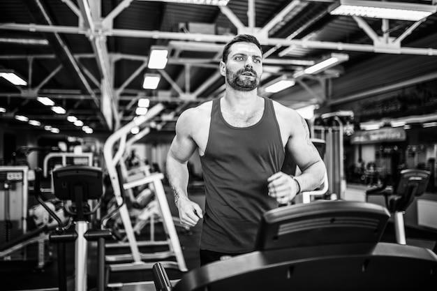 Muscle man loopt op loopband Premium Foto