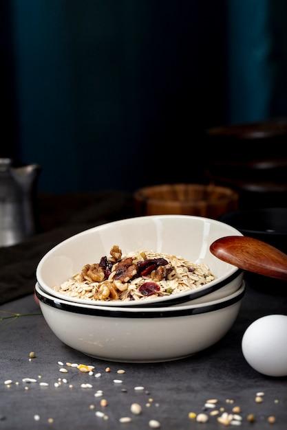 Musli in een witte kom en een houten lepel met een ei op een grijze achtergrond Gratis Foto