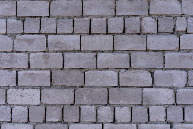 Muur van betonblokken als achtergrond en geweven Premium Foto