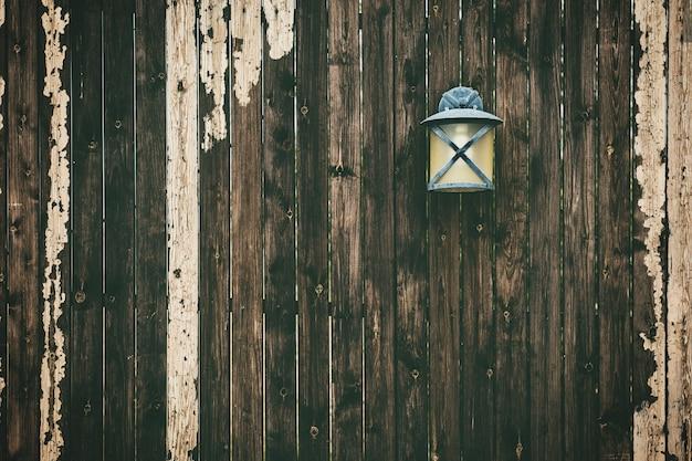 Muur van verweerde houten verticale planken met een oude lamp erop Gratis Foto