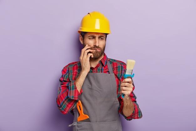 Muurschildering concept. ernstige doordachte vakman kijkt naar schone borstel, bijt onderlip, denkt na over de renovatie van zijn appartement, draagt gele hoofddeksels en schort, geïsoleerd op paarse muur Gratis Foto