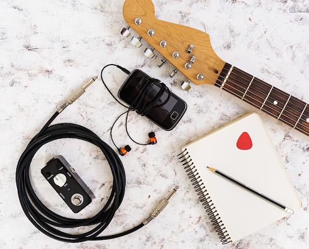 Muziek dingen. gitaar, gitaarpedaal, hoofdtelefoon, mobiele telefoon op wit Premium Foto