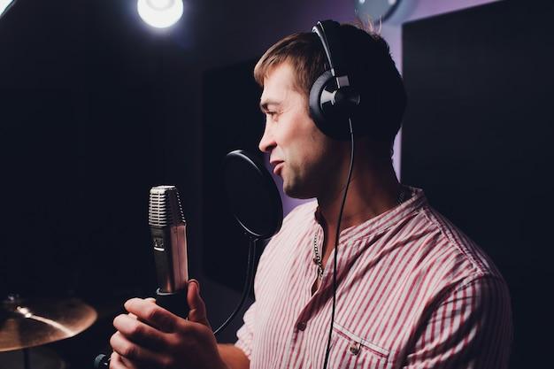 Muziek, showzaken, mensen en stemconcept - mannelijke zanger met hoofdtelefoons en microfoon het zingen lied bij geluidsopnamestudio. Premium Foto