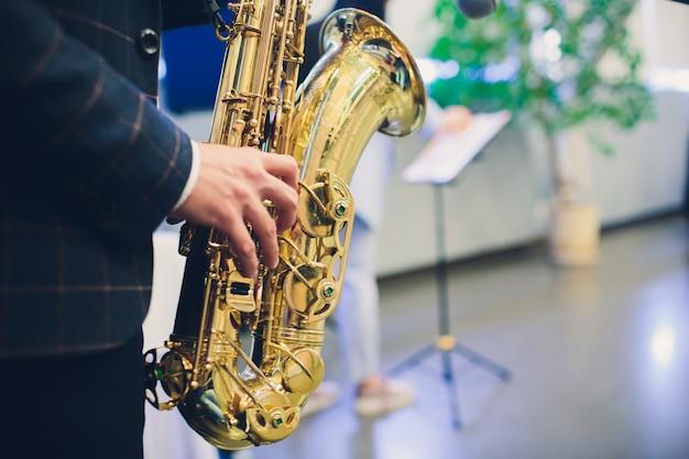 Muziekinstrumenten, saxofonist overhandigt saxofonist die jazzmuziek speelt. close-up van het altsaxofoon de muzikale instrument. Premium Foto