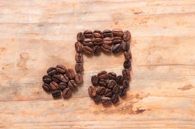 Muzieknoot van koffiebonen wordt gemaakt op houten achtergrond die Gratis Foto