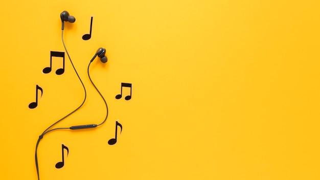 Muzieknoten en oortelefoons met exemplaarruimte Gratis Foto