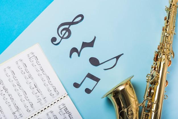 Muzikaal notitieboekje en gouden saxofoons op blauwe achtergrond Gratis Foto