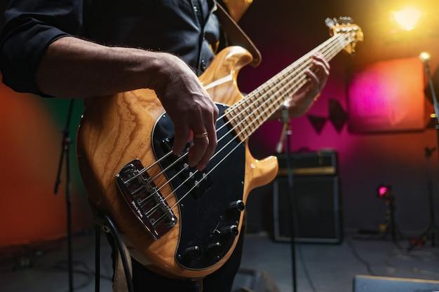 Muzikant speelt bas, close-up, opnamestudio Premium Foto