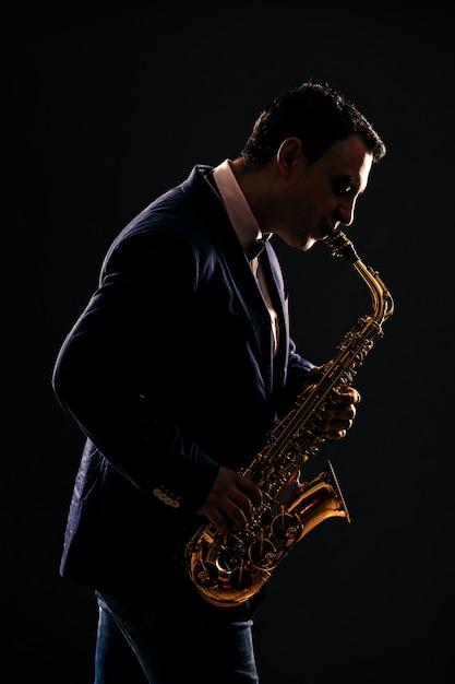 Muzikant speelt jazz op saxofoon. donker Premium Foto