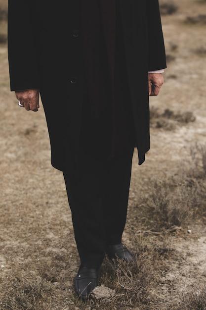 Mysterieuze man in zwart pak en schoenen Gratis Foto