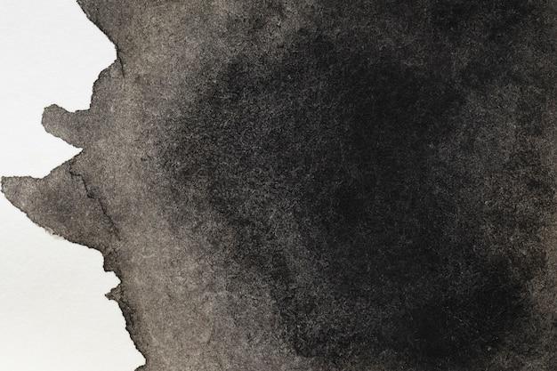 Mysterieuze zwarte handgeschilderde vlek op wit oppervlak Gratis Foto