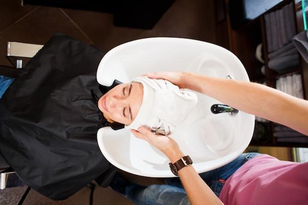 Na het wassen wikkelt de kapper het haar van de cliënt in een handdoek. bovenaanzicht Premium Foto