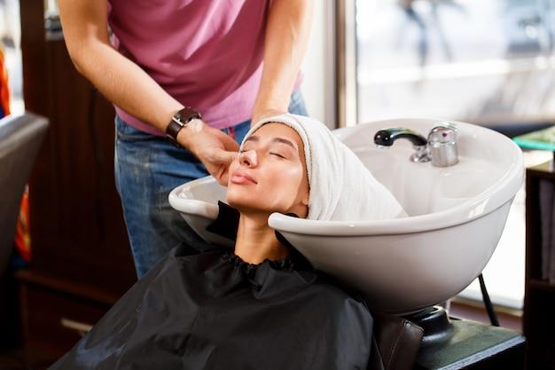 Na het wassen wikkelt de kapper het haar van de cliënt in een handdoek Premium Foto