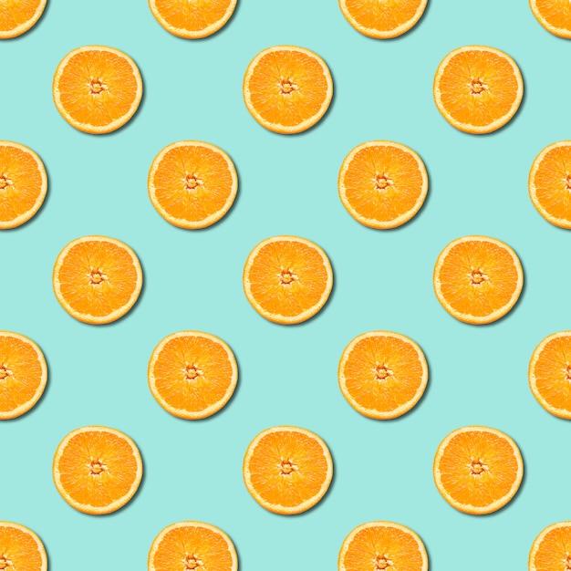 Naadloos patroon van sinaasappel dat op de neoachtergrond van de munt groene kleur wordt gesneden. minimaal, platliggend. Premium Foto
