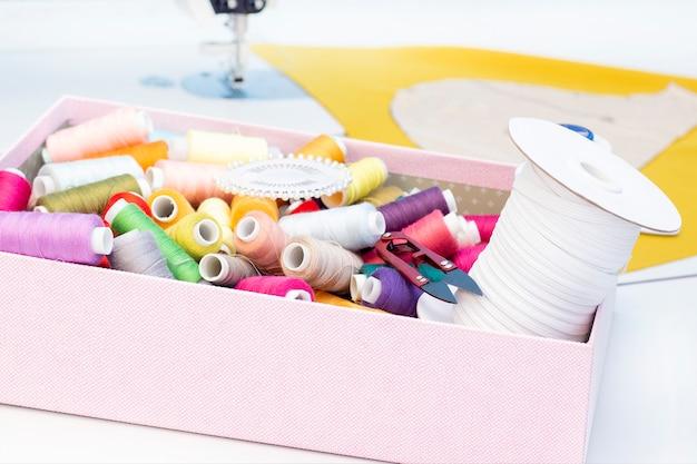 Naaiatelier. naaimachine. een set items voor handwerk: draden, naalden, pinnen, meetlint, enz. Premium Foto