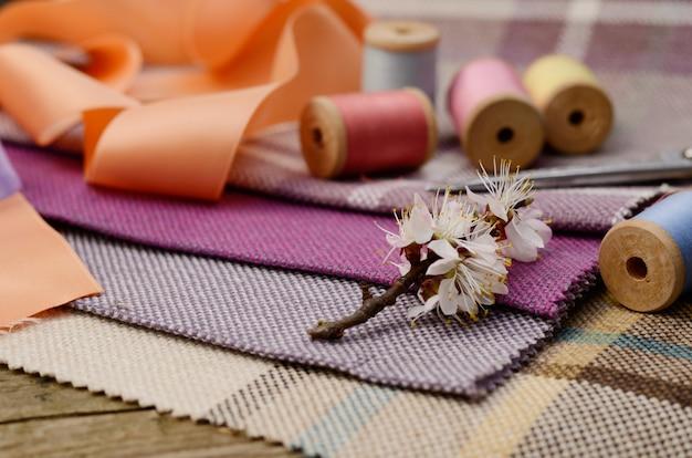 Naaibenodigdheden, naalden, schaar op het kleurrijke jute textiel Premium Foto